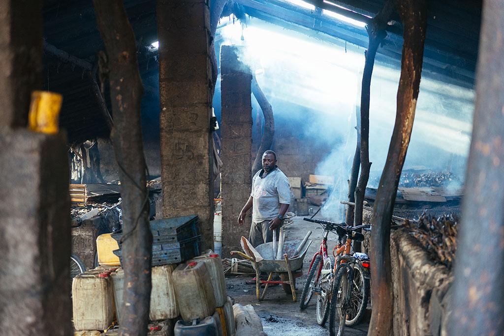 Hombre en el interior e un ahumadero de pescado en la playa de Tanji, Gambia