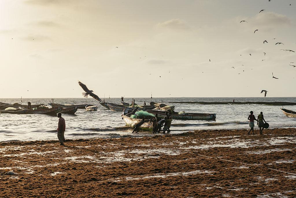 Hombres sacan su barca del mar en Tanji al atardecer