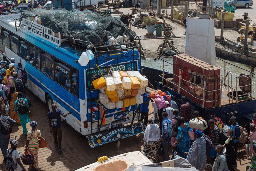 Camiones y pasajeros subiendo al ferri de Banjul a Barra